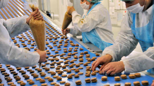 Employees work on an industrial French macarons' assembly line.
